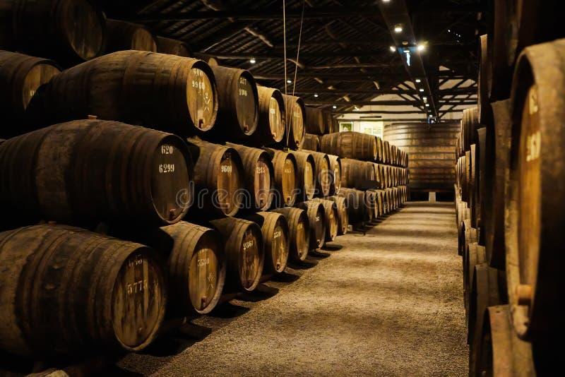 Velho envelheceu tambores de madeira tradicionais com vinho em um cofre-forte alinhado na adega fresca e escura em It?lia, Porto, fotografia de stock