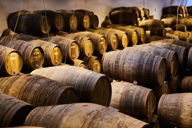 Velho envelheceu tambores de madeira tradicionais com vinho em um cofre-forte alinhado na adega fresca e escura em It?lia, Porto, foto de stock royalty free