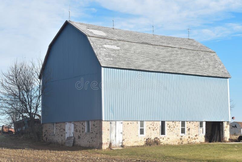 Velho ilumine - o celeiro azul com uma fundação da pedra de campo em uma exploração agrícola no outono atrasado em um dia ensolar fotografia de stock royalty free