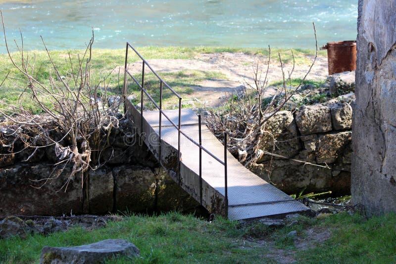 Velho improvisou a ponte oxidada parcialmente quebrada caseiro do metal sobre o canal estreito da água cercado com pedras e grama imagens de stock royalty free