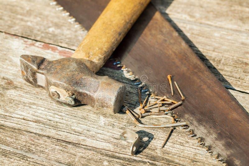 Velho martelo e serra sobre a mesa de madeira fotos de stock royalty free