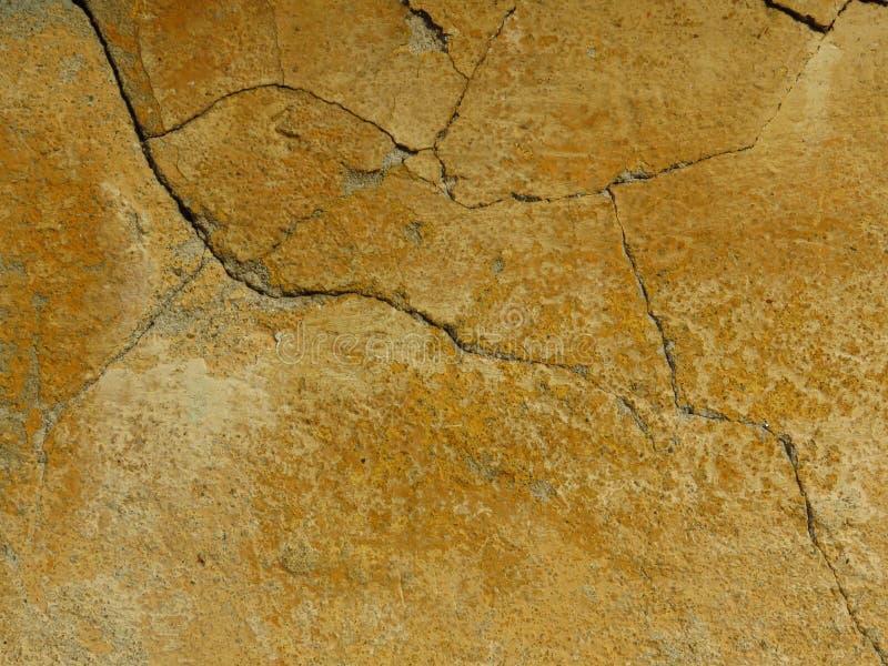 Velho rachou a parede concreta do cimento pintada no amarelo imagem de stock