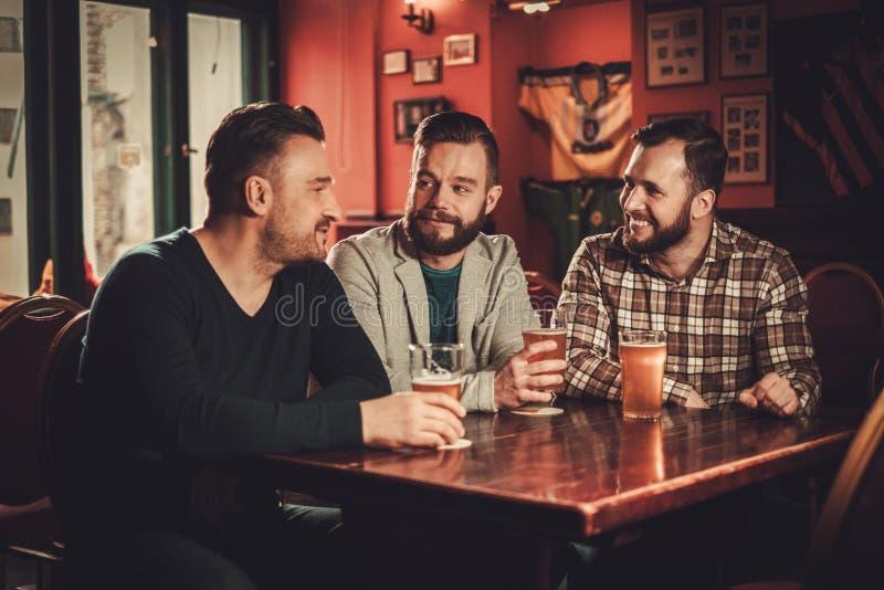 Velhos amigos alegres que têm o divertimento e que bebem a cerveja de esboço no bar imagens de stock