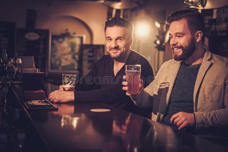 Velhos amigos que bebem a cerveja de esboço no contador da barra no bar imagens de stock