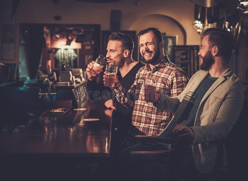Velhos amigos que têm o divertimento e que bebem a cerveja de esboço no contador da barra no bar fotos de stock royalty free
