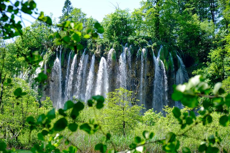 Veliki Prstavac Waterfall framed by green leaves and branches, at Plitvice Lakes Plitvicka Jezera, Croatia, in full bright light royalty free stock images