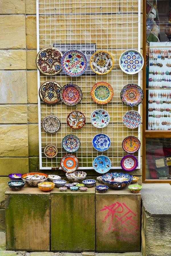 VELIKO TARNOVO, BULGARIJE - APRIL 03, 2015: De winkel in de voetstraat in de Oude stad, traditionele kleurrijke Platen is met de  stock foto's