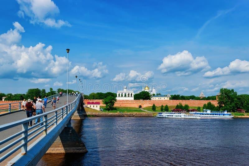 Veliky Novgorod, Rusia - 14 de junio de 2015: Paredes del fortalecimiento del Kremlin y gente en el puente sobre el río de Volkho foto de archivo libre de regalías