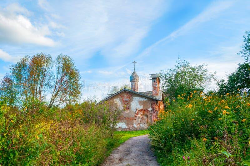 Veliky Novgorod, Rusland Kerk van St John Mild in Myachino in Veliky Novgorod, Rusland De mening van de herfst Oranje bladeren op royalty-vrije stock fotografie