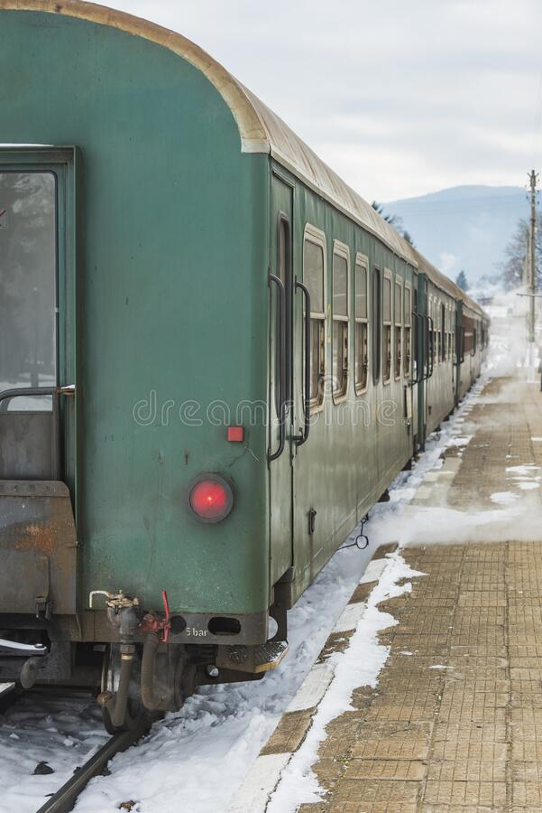 Velingrad railway station, Bulgaria - February 8, 2020: Train with red locomotive and green wagons departures at the train station.  royalty free stock photography