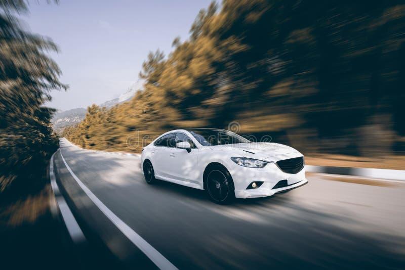 Velocidad blanca del coche que conduce en la carretera de asfalto imagen de archivo libre de regalías