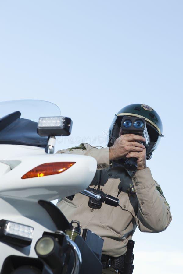 Velocidad de la supervisión del poli de tráfico a través del radar contra el cielo imágenes de archivo libres de regalías