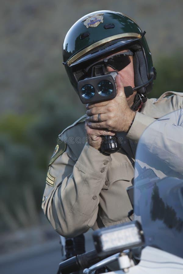 Velocidad de la supervisión del policía a través del radar mientras que se sienta en la bici imagenes de archivo