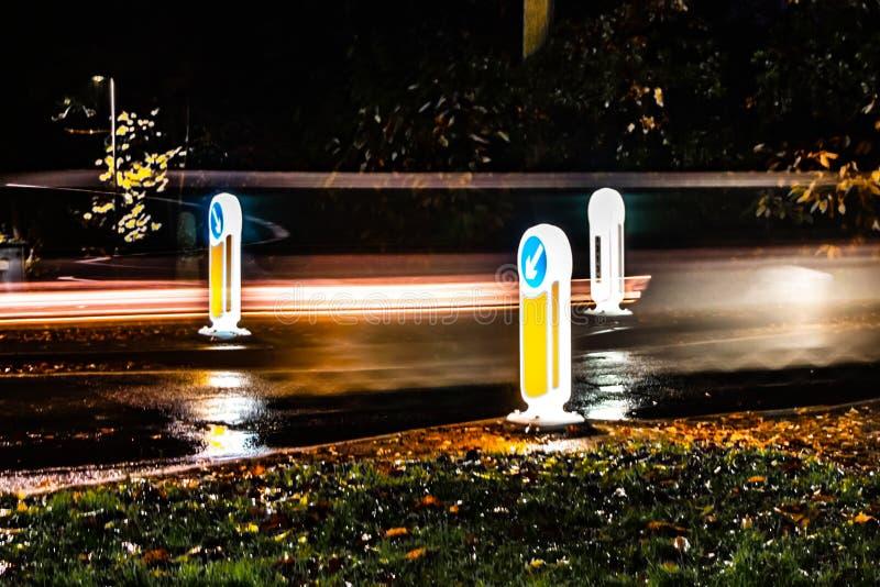 Velocidad del camino, señales de tráfico con el fondo oscuro con la luz de pasar el coche fotografía de archivo