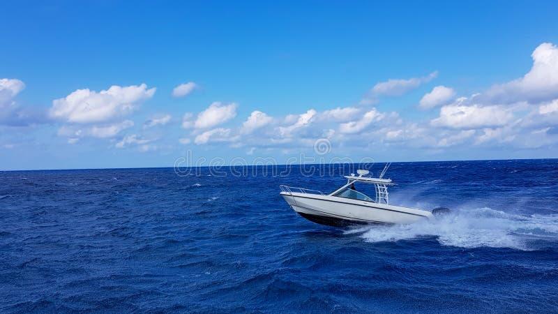 Velocidad que pesca el barco blando que salta las ondas en el mar y que cruza el día azul del océano en Bahamas Agua hermosa azul imagenes de archivo