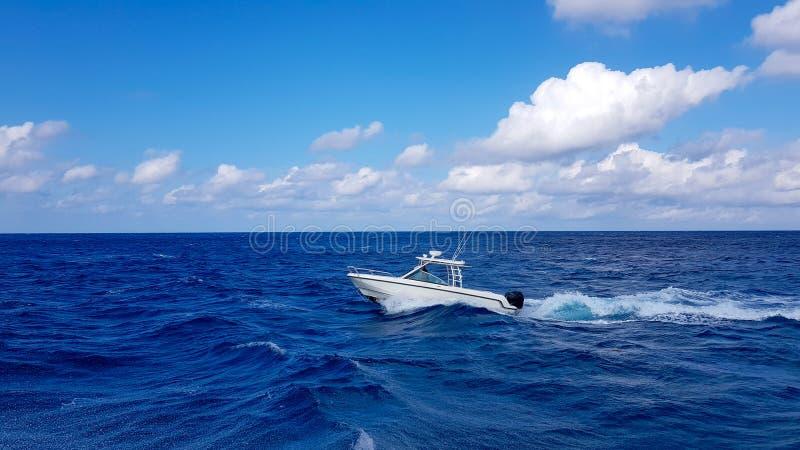 Velocidad que pesca el barco blando que salta las ondas en el mar y que cruza el día azul del océano en Bahamas Agua hermosa azul fotos de archivo