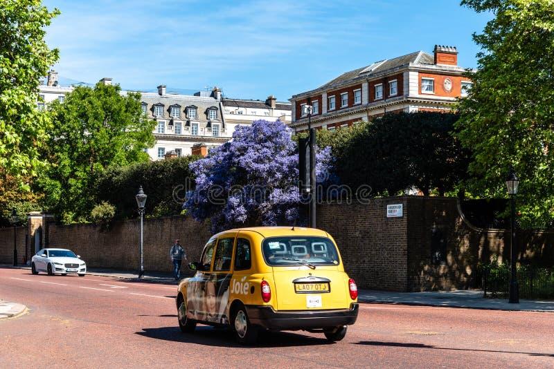 Velocidade amarela do táxi através da estrada em Londres fotografia de stock royalty free