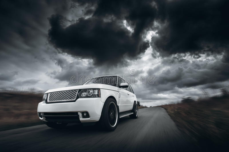 Velocidade branca do carro que conduz na estrada no dia dramático das nuvens imagens de stock