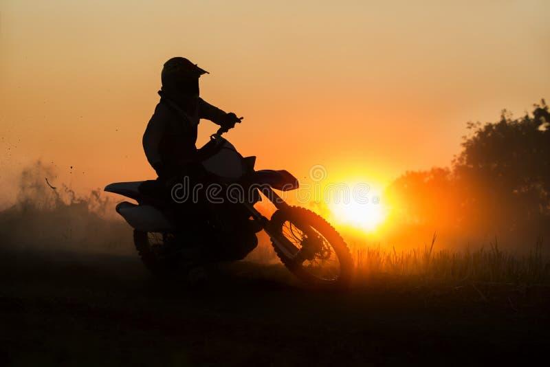 Velocidade do motocross da silhueta na trilha imagem de stock