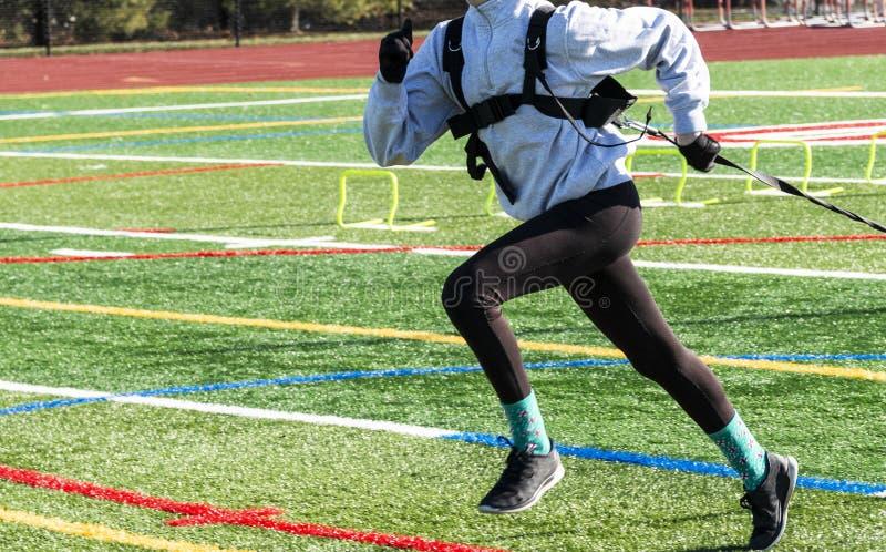Velocista fêmea da trilha que corre puxando o trenó imagem de stock