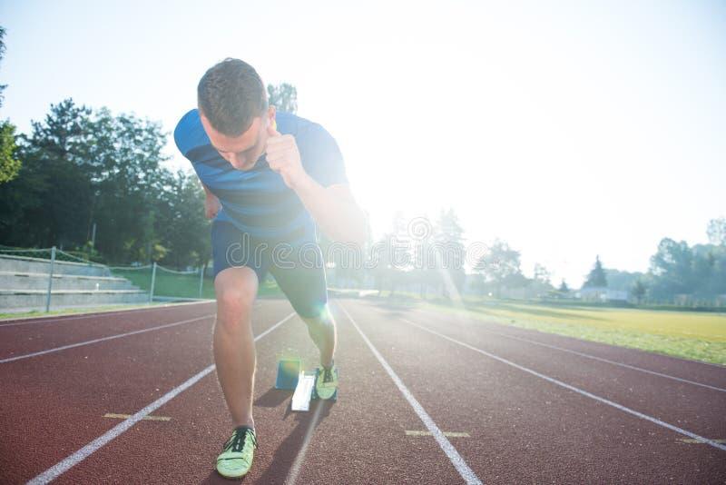 Velocista que deixa blocos começar na pista de atletismo Começo explosivo foto de stock royalty free