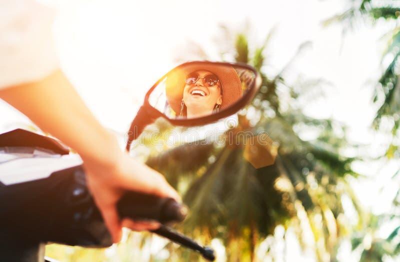 Velomotor de sorriso da equitação da mulher espelhado no espelho de rearview com raios de sol de brilho no fundo Povos alegres du fotografia de stock royalty free