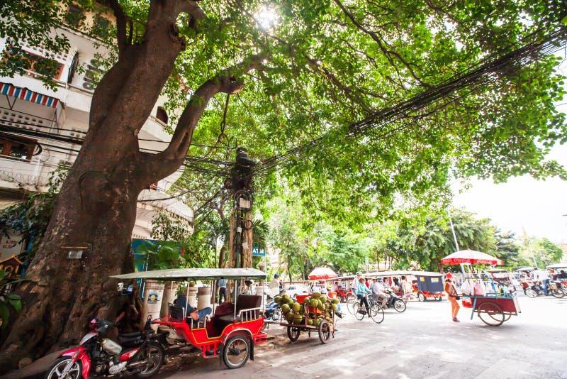 Velomotor do triciclo estacionado pelo obscuro da árvore, do vendedor ambulante e do veículo velhos na rua da manhã Phnom Penh, C imagem de stock
