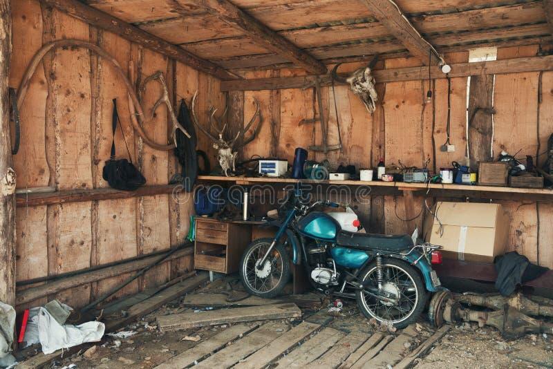 Velomotor velho em um celeiro pitoresco Motocicleta do vintage no hangar velho com muitos objetos raros fotos de stock