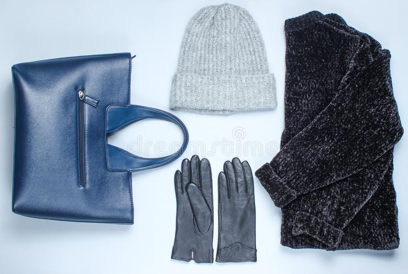 Velor black sweater, bag, leather gloves, warm wool. Hat on a gray background. Top view. Flat lay style royalty free stock photo