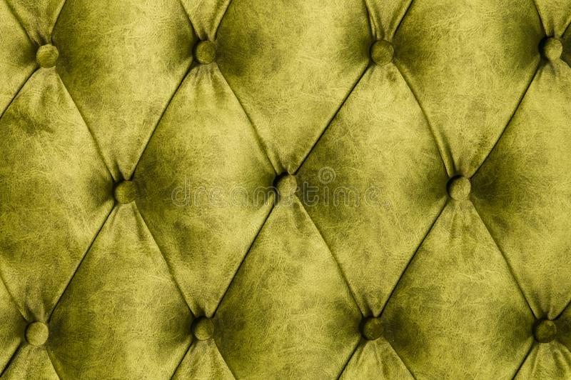 Velor lime surface of sofa close-up. Training equipment-velor mats tightened with buttons. Yellow chesterfield style stock image