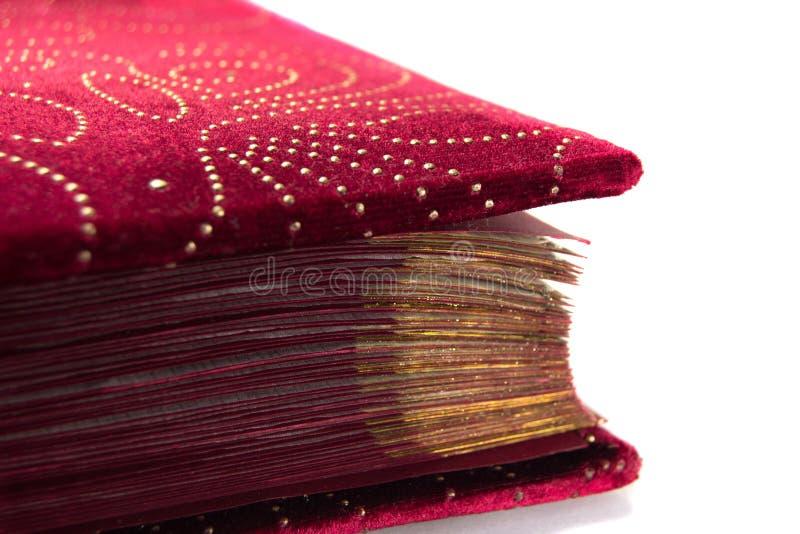 Veludo vermelho com as páginas douradas do livro isoladas no fundo branco fotos de stock royalty free