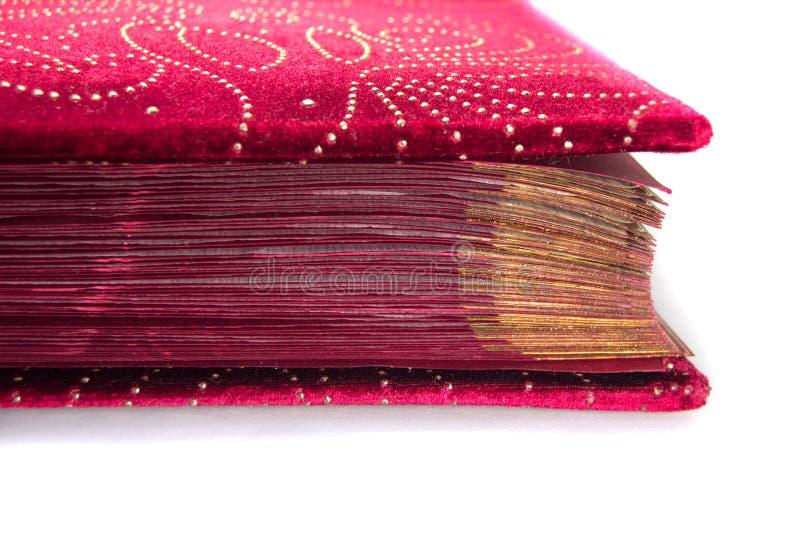 Veludo vermelho com as páginas douradas do livro isoladas no fundo branco imagens de stock royalty free
