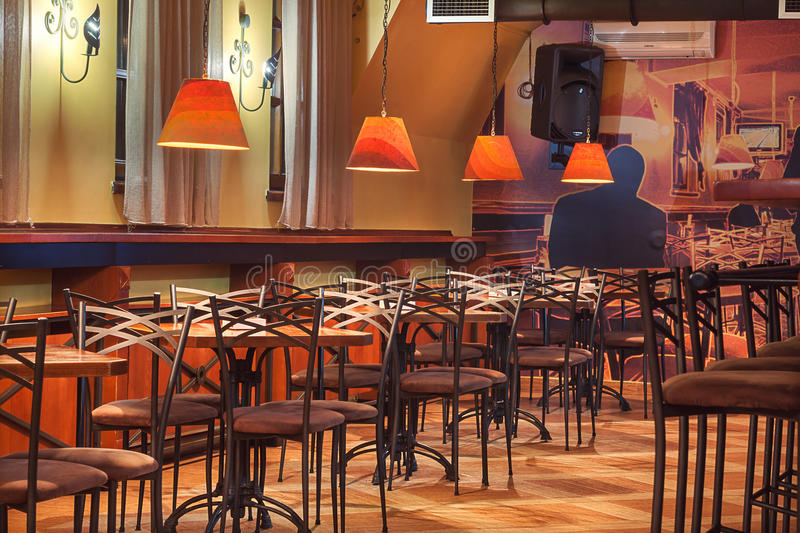 Velvet Cafe. Cacak, Serbia - January 23, 2015: Velvet Cafe and Club interior, modern design with vintage chairs and tables and illustrative wallpapers royalty free stock photos