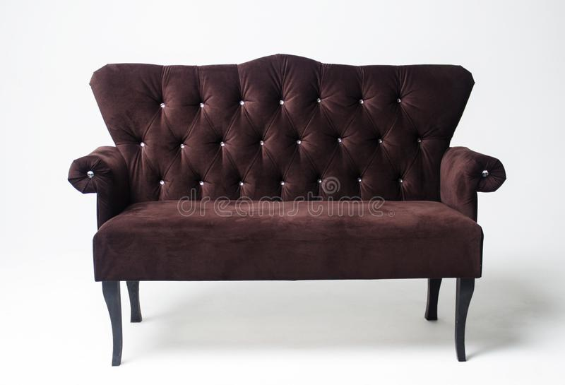 Velvet classic sofa on a light background. Brown sofa with wooden legs royalty free stock images