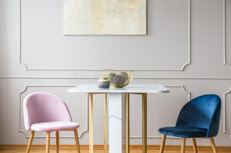 Velvet pastel pink and petrol blue chairs at small dining table in living room. Velvet pastel pink and petrol blue chairs at small dining table in bright living royalty free stock images