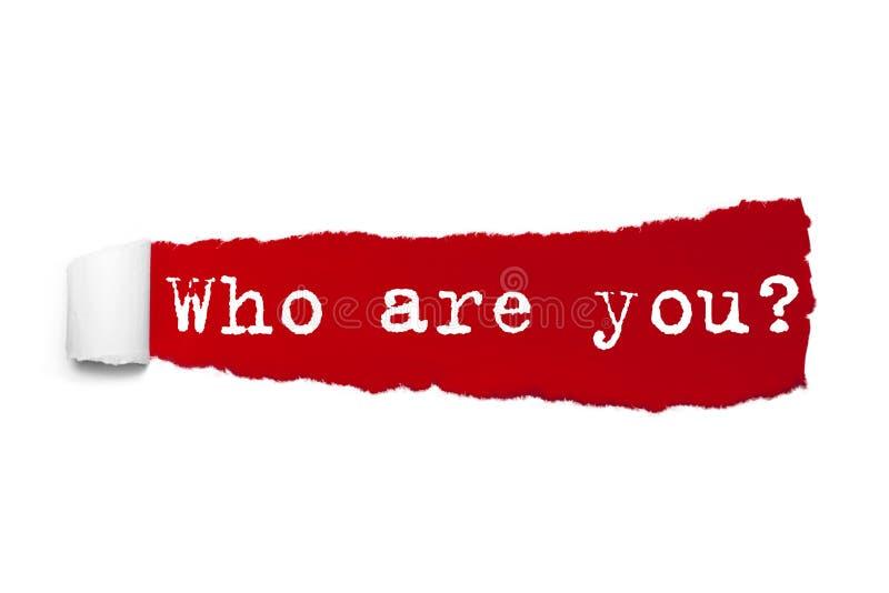 Vem är dig frågan som är skriftlig under det krullade stycket av rött sönderrivet papper arkivbild