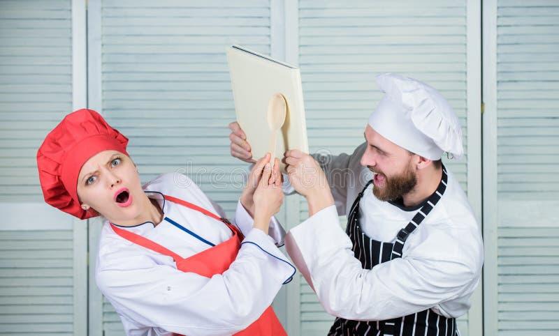 Vem är i laddningen av köket par som ?r f?r?lskade med perfekt mat Man- och kvinnakock Familjmatlagning i k?k hemlighet arkivfoto