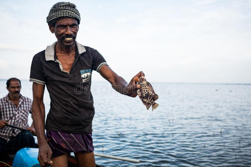 Vembanad lake, Kerala - 20 october 2019: portrait of an indian fisherman on a boat fishing and showing fish, a symbol of indian royalty free stock images