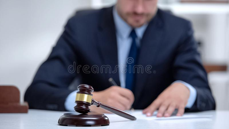 Venal judge filling in documents and insurance, passing sentence, profession royalty free stock photos