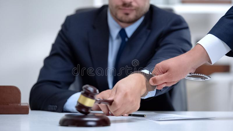 Venal judge handcuffed when passes unfair sentence, instant punishment for bribe royalty free stock photography