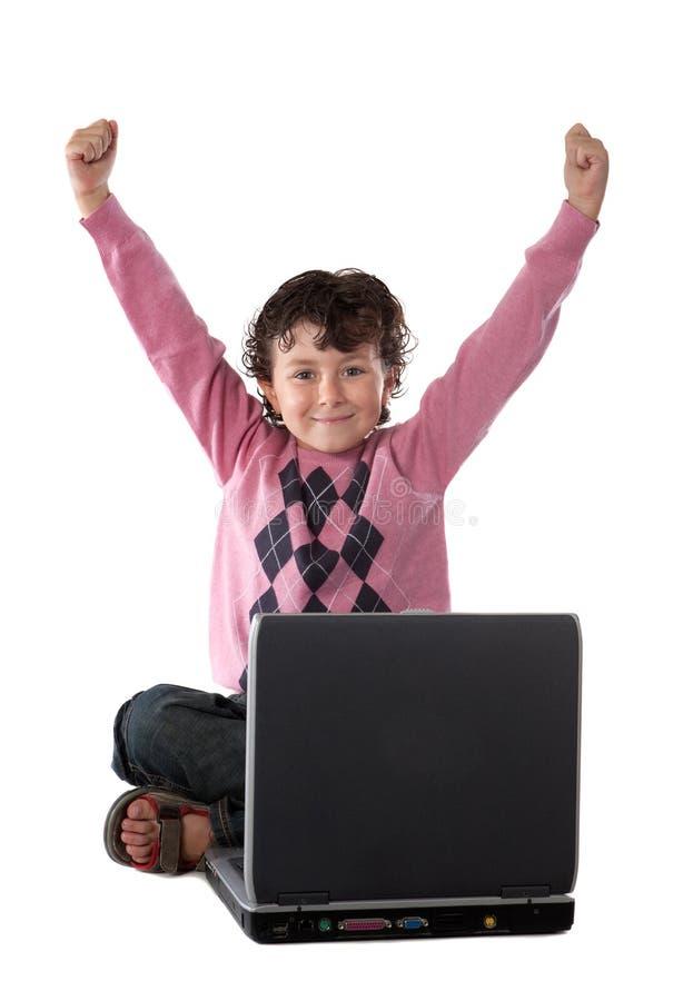 Vencedor feliz da criança que senta-se com um portátil fotografia de stock