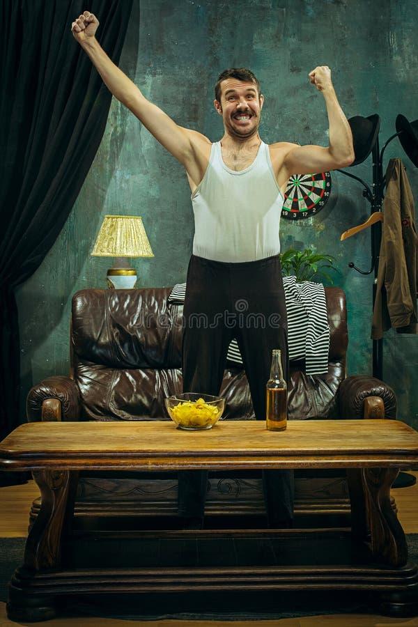 vencedor Mãos moventes oprimidas do homem alegre ao comemorar a vitória de uma equipa de futebol favorita fotografia de stock