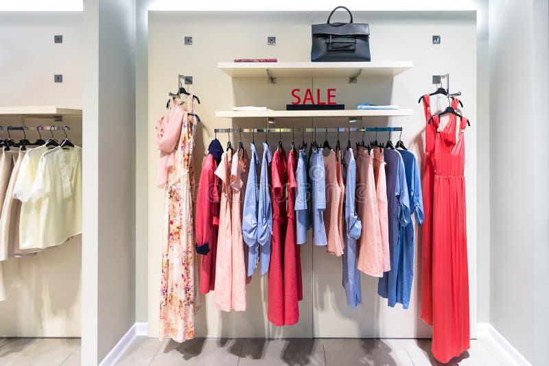A venda assina dentro a loja de roupa das mulheres Vestidos coloridos em ganchos em uma loja varejo Venda da estação, forma e con imagens de stock