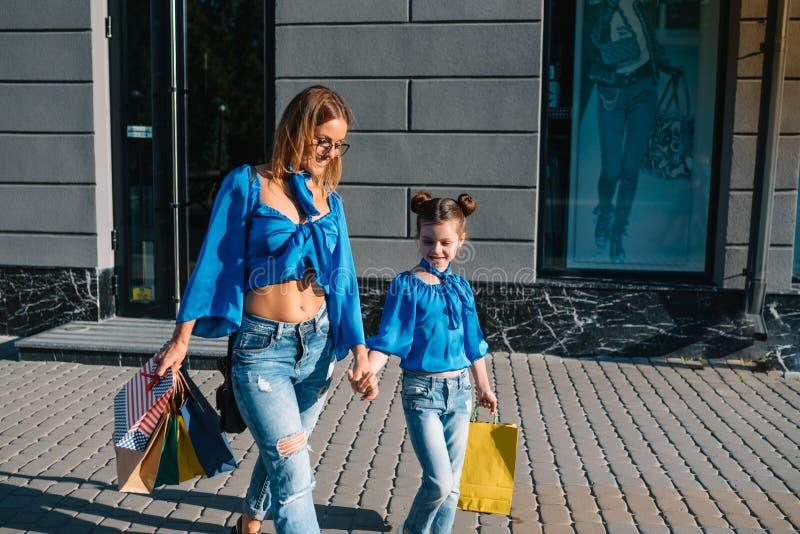 Venda, consumismo e conceito de pessoas - mulheres jovens felizes sua filha com sacos de compras andando pela rua foto de stock royalty free