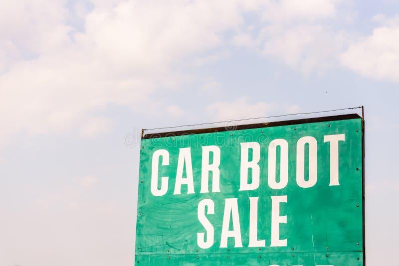 Venda da bota do carro este sinal de domingo com o céu no bachground imagem de stock