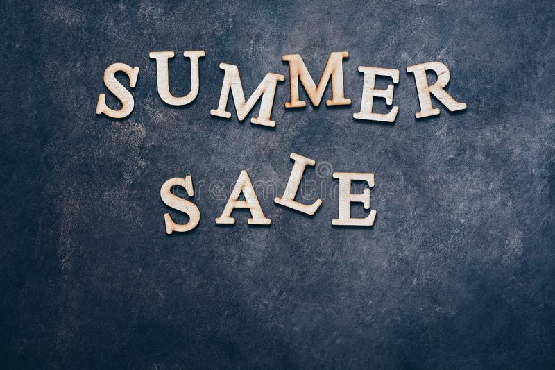 Venda-texto do verão em letras de madeira em um fundo rústico escuro, configuração lisa, espaço da cópia ilustração royalty free