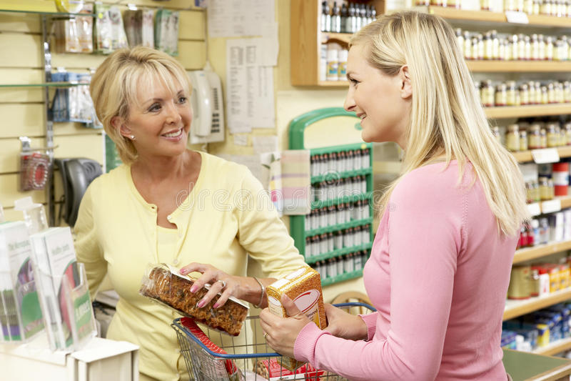 Vendas assistentes com o cliente na loja do alimento natural fotografia de stock royalty free