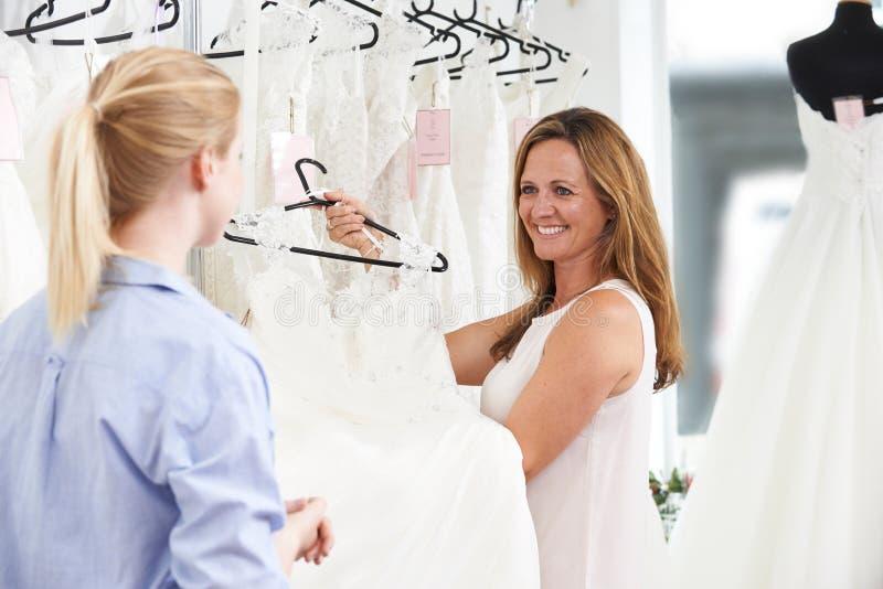 Vendas assistentes na noiva de ajuda da loja nupcial para escolher o casamento foto de stock royalty free