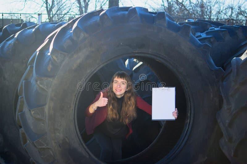 Vendas atrativas de um trabalhador fêmea dos pneus e dos pontos à prancheta imagem de stock