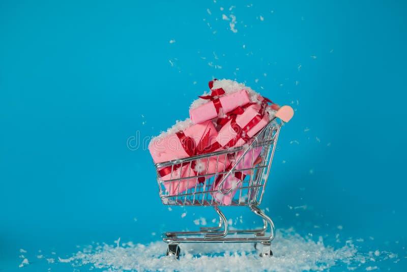 Vendas do Natal Presentes de compra pelo ano novo, o conceito O carrinho de compras está completo das caixas de presente fotografia de stock